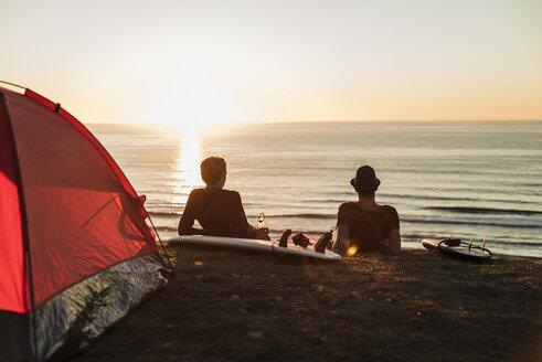 Two best friends enjoying sunset on the beach - UUF08808