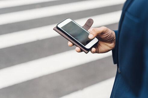 Businessman holding smart phone - GIOF01510