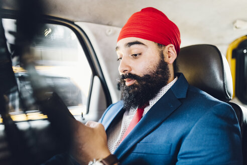 Indian businessman using smartphone in taxi - GIOF01525