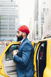 Indian businessman in Manhattan entering a yellow cab - GIOF01531