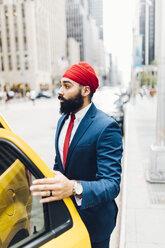 Indian businessman in Manhattan entering a yellow cab - GIOF01534