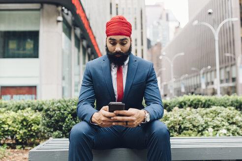 Indian businessman sitting in Manhattan, using smartphone - GIOF01540