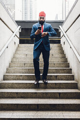 Indian businessman walking down stairs, looking at watch , holding smartphone - GIOF01543