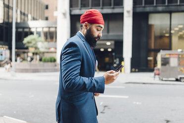 Indian businessman in Manhattan using smartphone, walking in the street - GIOF01549