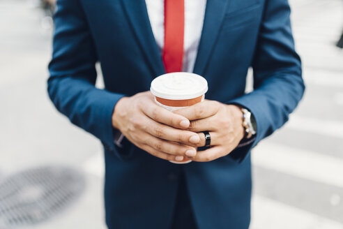 Businessman walking in the city, holding cup of coffee - GIOF01552