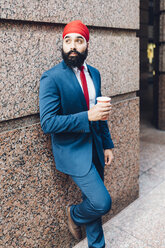 Indian businessman in Manhattan leaning against wall, drinking coffee - GIOF01561