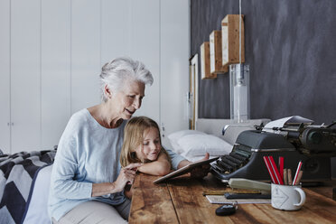 Grandmother and granddaughter looking at tablet at home - RORF00318