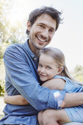 Father and daughter hugging outdoors - RORF00348