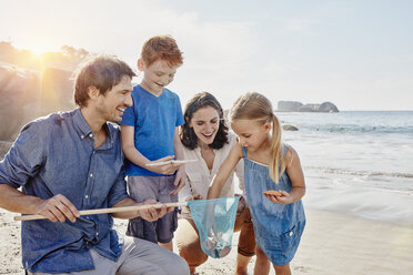 Happy family with dip net on the beach - RORF00357