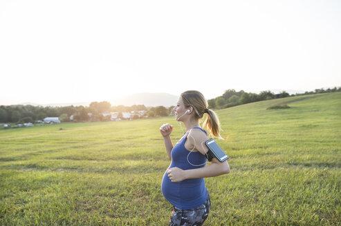 Pregnant woman jogging in field - HAPF01007