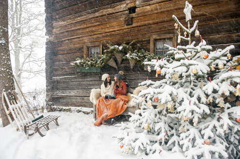 Friends sitting on bench by Christmas tree in front of mountain hut - HHF05433