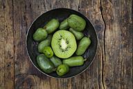 Bowl of sliced and whole hardy kiwis and half of kiwi on dark wood - LVF05455