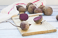 Whole and sliced beetroots on wooden board - LVF05477