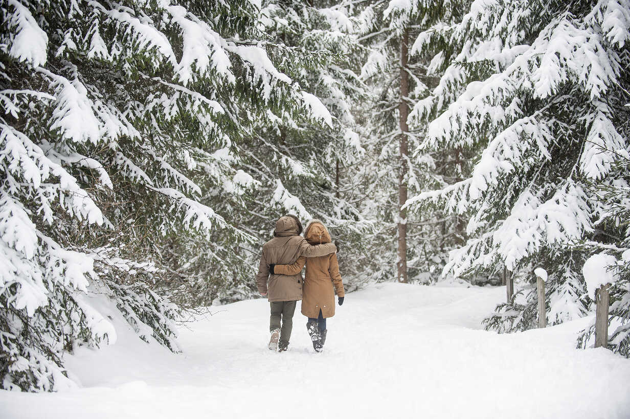 Happy couple walking in winter forest - HHF05444 - Hans Huber/Westend61