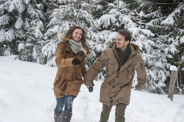 Happy couple walking in winter forest - HHF05447