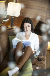 Reading woman sitting in hotel lounge with glass og red wine - HHF05450