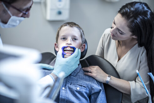 Boy with mother in dental surgery receiving orthodontic treatment - ZEF10626