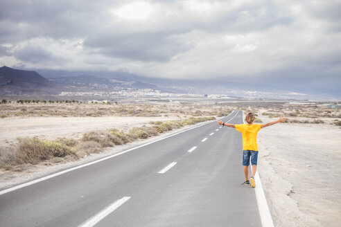 Spain, Tenerife, back view of boy with arms outstretched walking on empty country road - SIPF00942