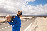 Spain, Tenerife, boy with skateboard beside empty country road looking at distance - SIPF00945