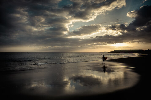 Spain, Tenerife, boy carrying surfboard on the beach at sunset - SIPF00960