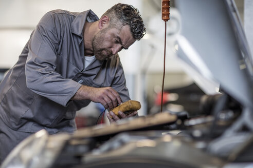 Car mechanic in a workshop using diagnostic equipment - ZEF10705