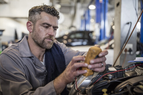 Car mechanic in a workshop using diagnostic equipment - ZEF10711