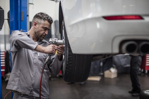 Car mechanic in a workshop changing tire - ZEF10714