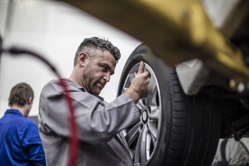 Car mechanic in a workshop changing tire - ZEF10717