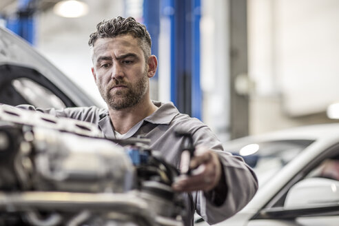 Car mechanic in a workshop working on engine - ZEF10723