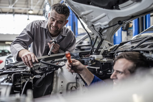 Two car mechanics in a workshop repairing car together - ZEF10726