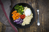 Lunch bowl of quinoa, red cabbage, carrots, roasted chickpeas, broccoli, poached egg and ajvar - LVF05480