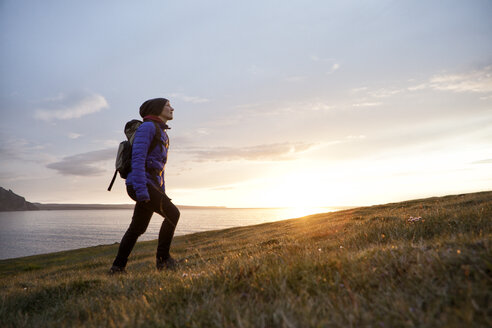 Iceland, woman hiking at twilight upon a hill - RBF05212