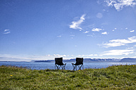 Iceland, two camping chairs on a meadow - RBF05221