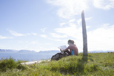 Iceland, hiker resting on a meadow looking at map - RBF05224