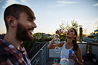 Young woman blowing soap bubbles on roof terrace - AIF00406
