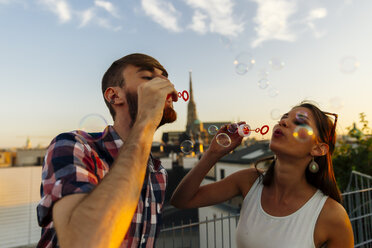 Austria, Vienna, young couple blowing soap bubbles on roof terrace - AIF00409