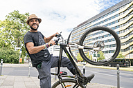 Portrait of smiling man with bicycle - TAMF00698
