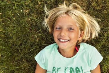 Portrait of smiling blond girl lying on a meadow - MGOF02544