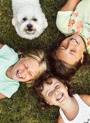 Three happy girls and a puppy on a meadow - MGOF02547