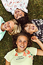 Four laughing girls lying head to head on a meadow - MGOF02550