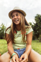 Portrait of smiling girl wearing summer hat sitting on a meadow - MGOF02553