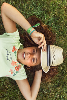 Portrait of girl with straw hat lying on a meadow - MGOF02556