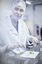 Smiling woman wearing protective clothing in lab examining plant sample - ZEF10841