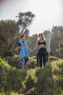 Teenage boy with down syndrome and woman hand in hand with surfboard at the coast - ZEF10860