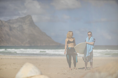 Teenage boy with down syndrome and woman with surfboard on beach - ZEF10863