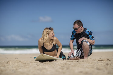 Teenage boy with down syndrome having surf lessons on beach - ZEF10869