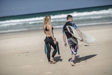 Teenage boy with down syndrome and woman with surfboard on beach - ZEF10872