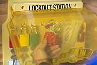 Hand taking lock from lockout station - ZEF10908