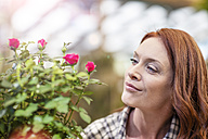 Woman in garden center with potted flowers - ZEF10971