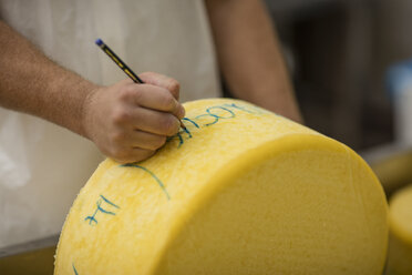 Cheese factory worker labelling cheese wheel - ZEF11010